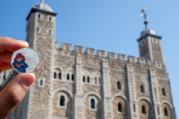 The coins depict Paddington Bear visiting the Tower of London and St Paul's Cathedral in London.