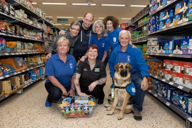 Julie Scott (front centre) and Morrisons colleagues with Mojo and Guide Dogs Scotland staff