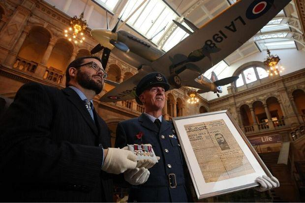 Glasgow Museums curator John Messner and Squadron leader Archie McCallum, of 602 Squadron City of Glasgow, with the front page announcing the death of Archie McKellar