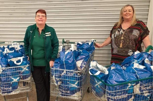 Julie Scott, community champion at the Morrisons store in Johnstone, delivers bags of donations to Provost Lorraine Cameron (right)