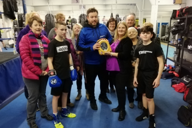 Colin and gym members receive the defibrillator